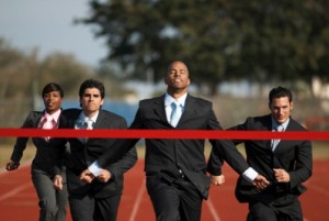 Men in suites running on a track crossing a red ribbon finish line