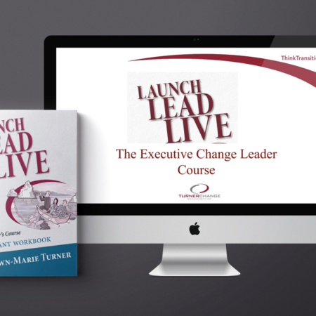 computer and book with launch lead live executive change leader course on the cover