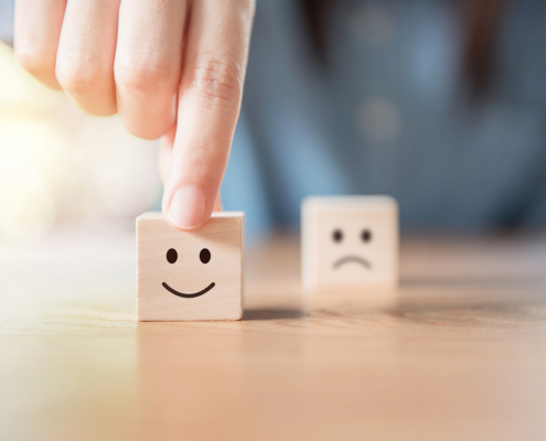 Hand overtop a wooden block with a smile on it, wooden block with a sad face out of focus in the background