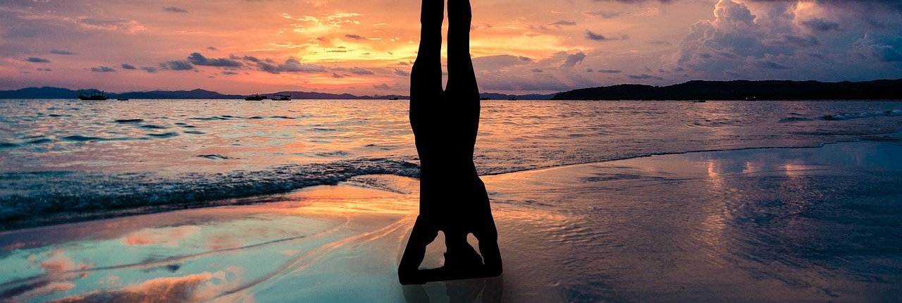 woman on beach at sunset doing headstand